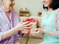 elderly-senior-woman-takes-gift-from-caregiver